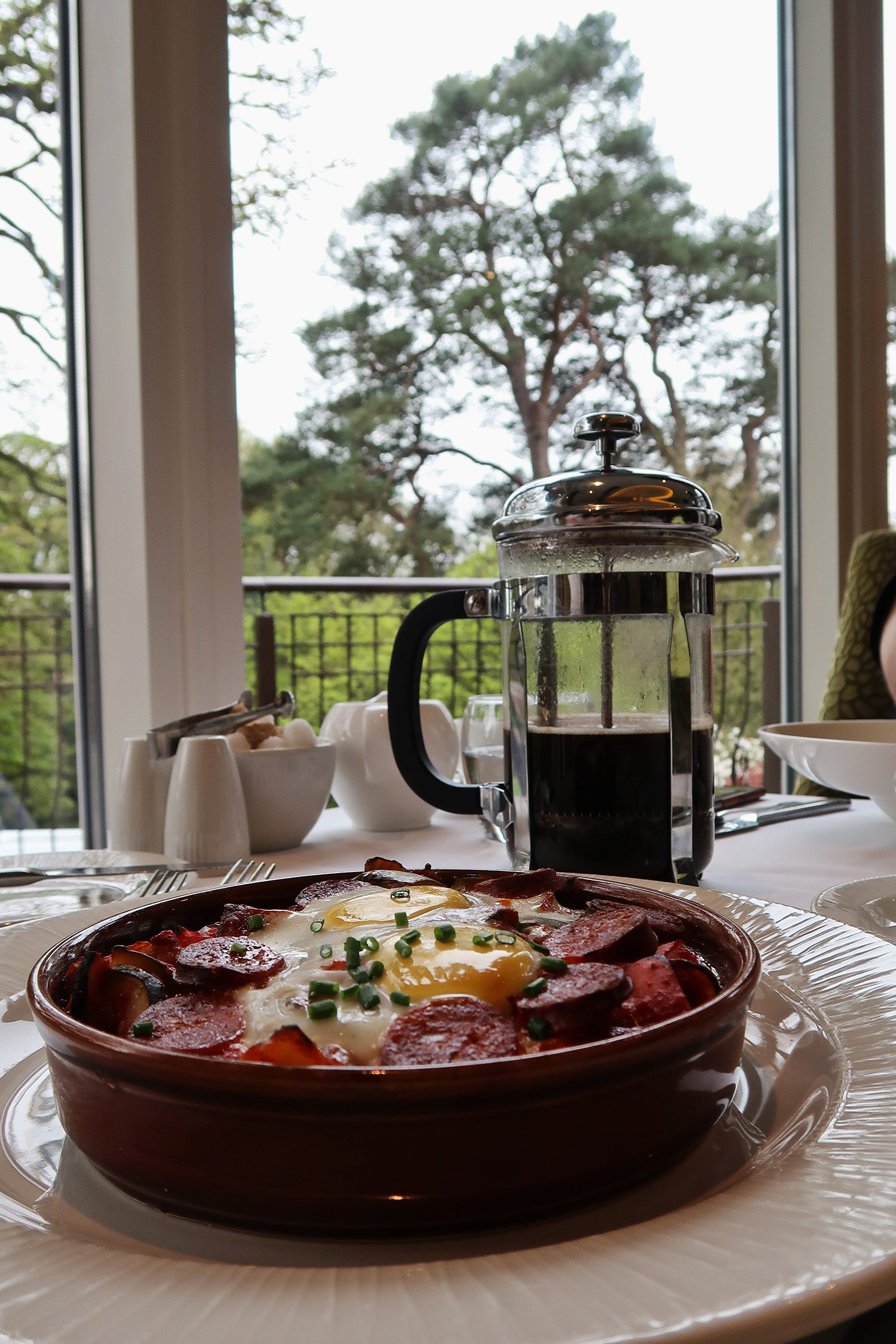 Bowl of chorizo and eggs with a pot of coffee and in the background the window looks out into the gardens