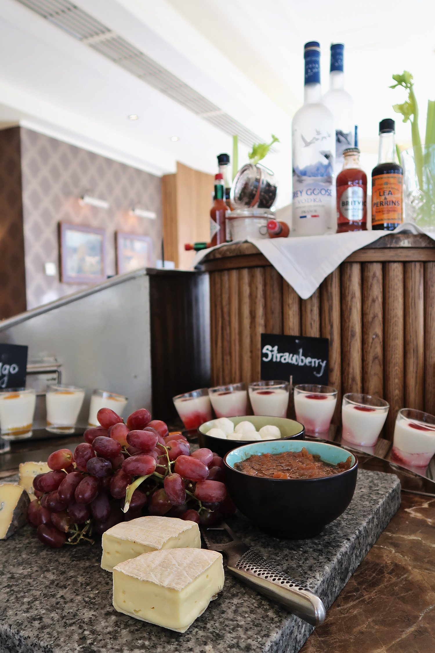 Cheese platter with grapes, pots of yoghurt and granola, and at the back the bottles of ingredients to make a bloody mary