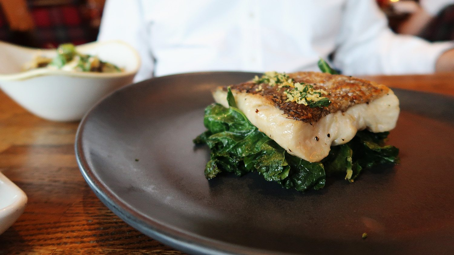 Close up of a plate of wilted spinach and grilled hake on a plate