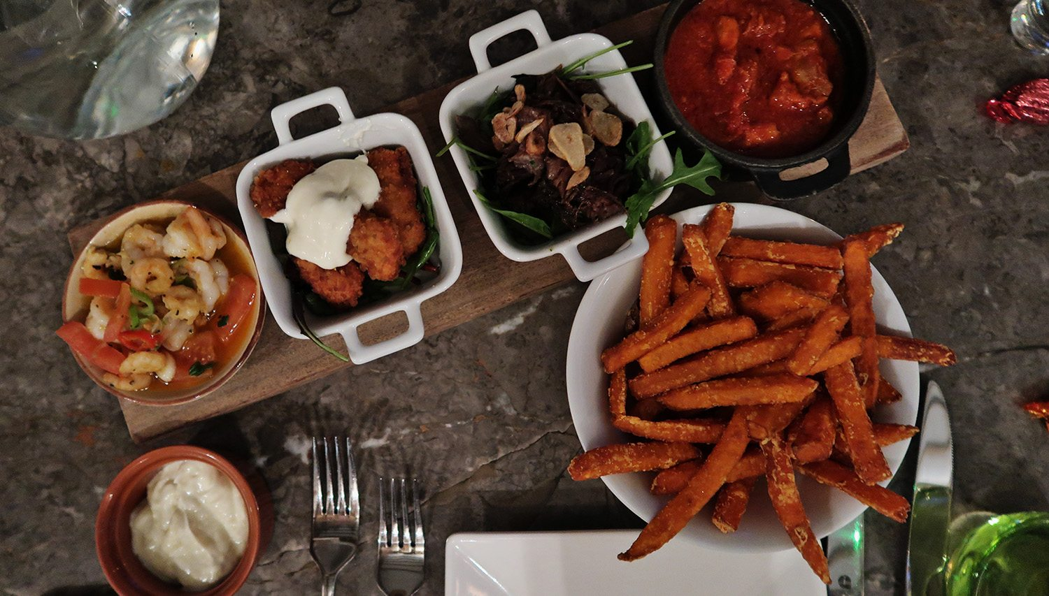Top view of 4 tapas plates and a bowl of sweet potato fries