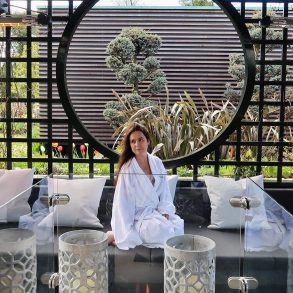 Woman in a white spa robe sits in an outside seating area with a modern firepit in the foreground