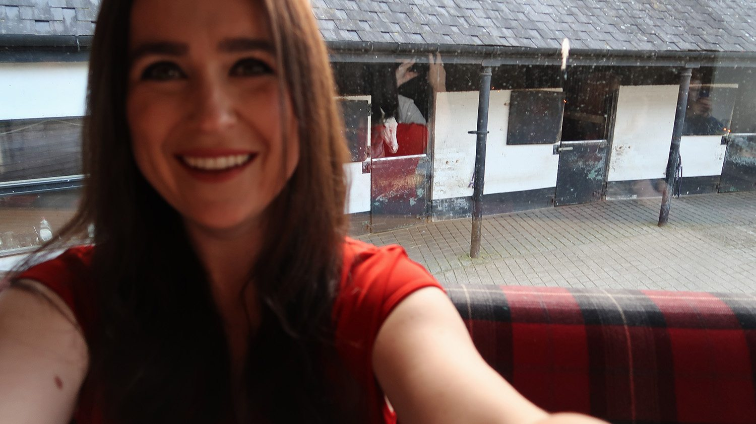 Selfie of a woman in a red top, behind her through the window you can see some stables and horse looking out of one.
