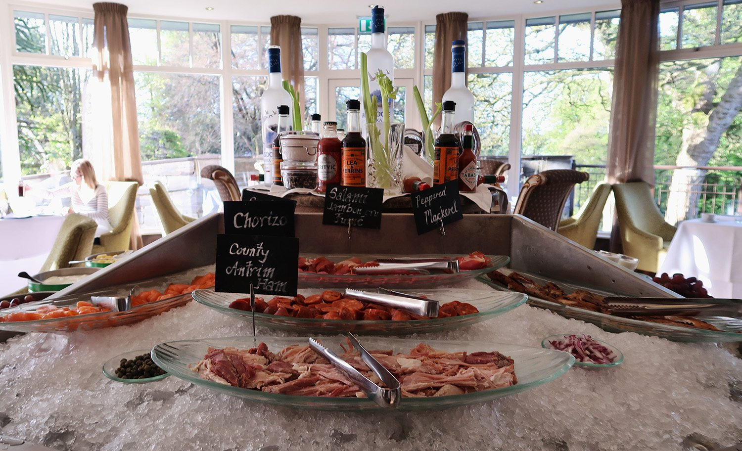 A large ice table with plates of meats and in the background are the bottles of ingredients to make a bloody mary