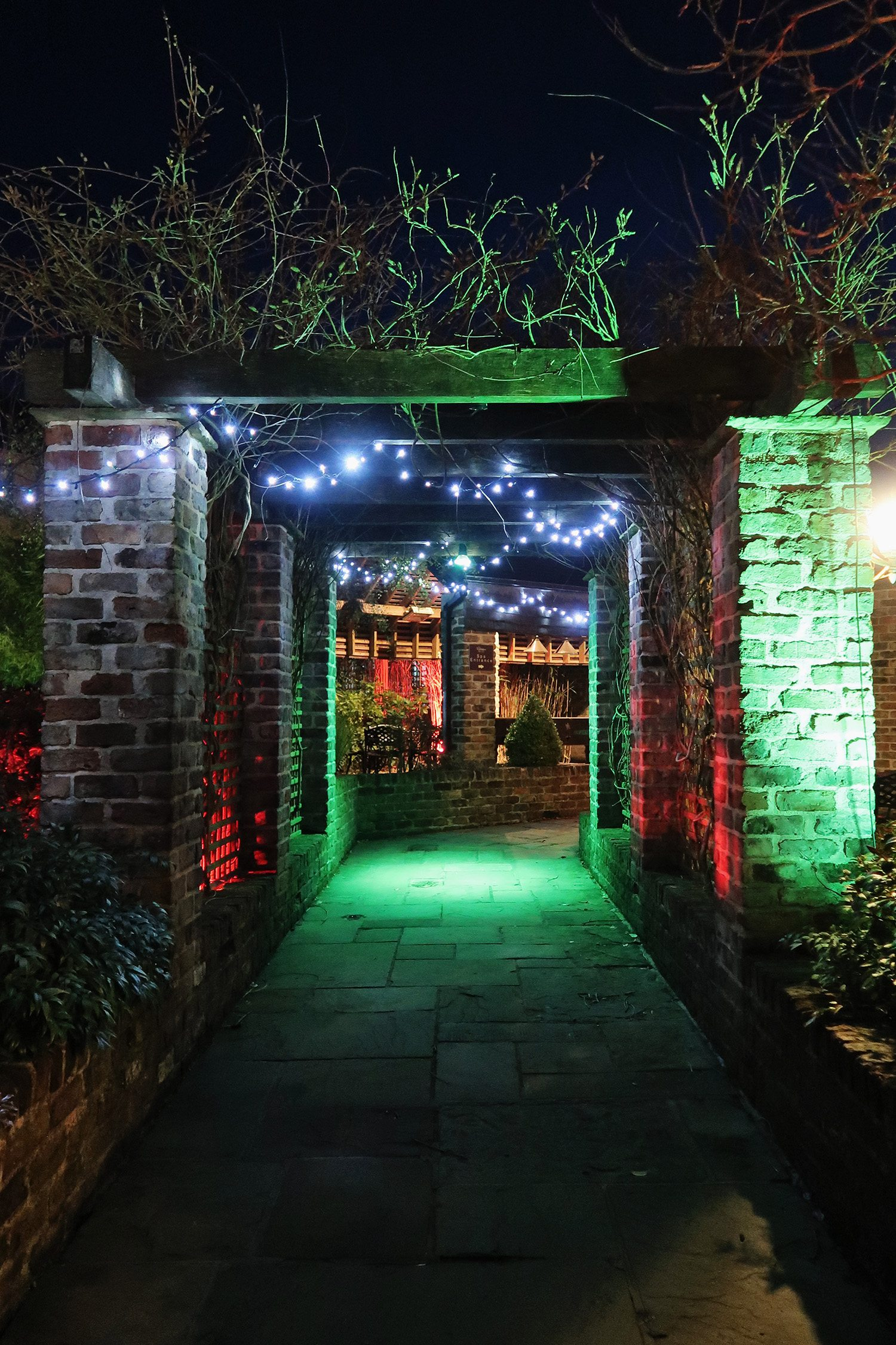 Nightime view of a brick gate entrance lit with coloured lights