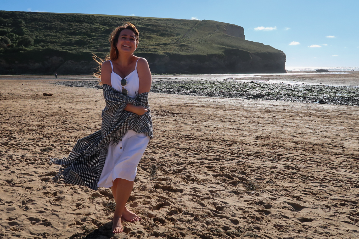 woman in white summer dress and checked wrap standing on beach in the sunshine smiling