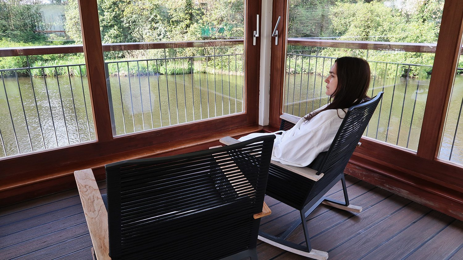 Woman in white spa robe sits in rocking chair looking out at the river through large windows from a meditation room