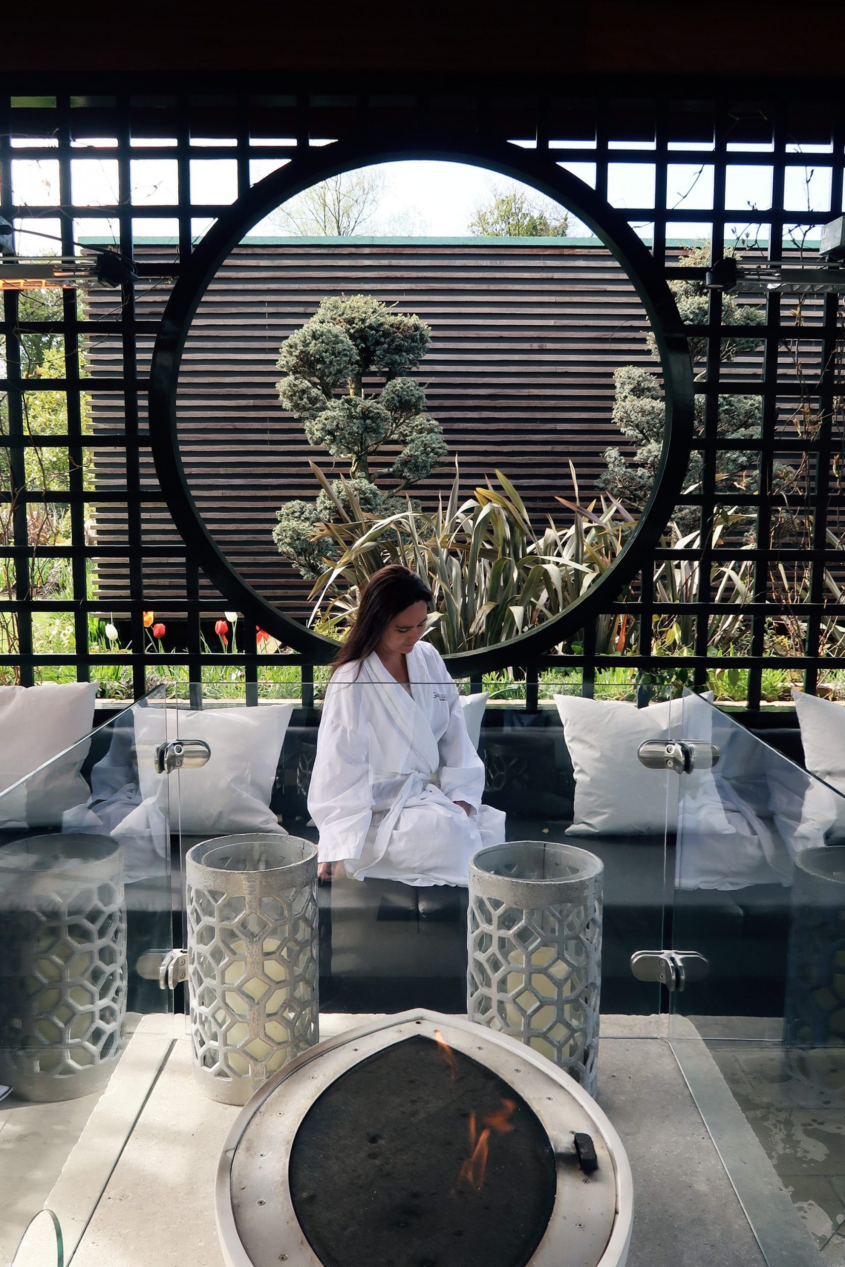 Woman in white spa robe snuggling up on outdoor sofas by the fire pit