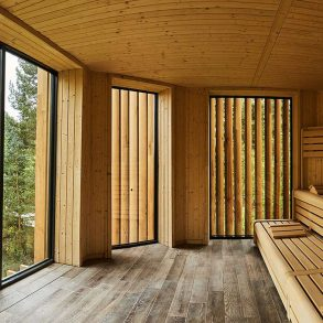 Wooden sauna with large window on the left looking out over the tree canopy