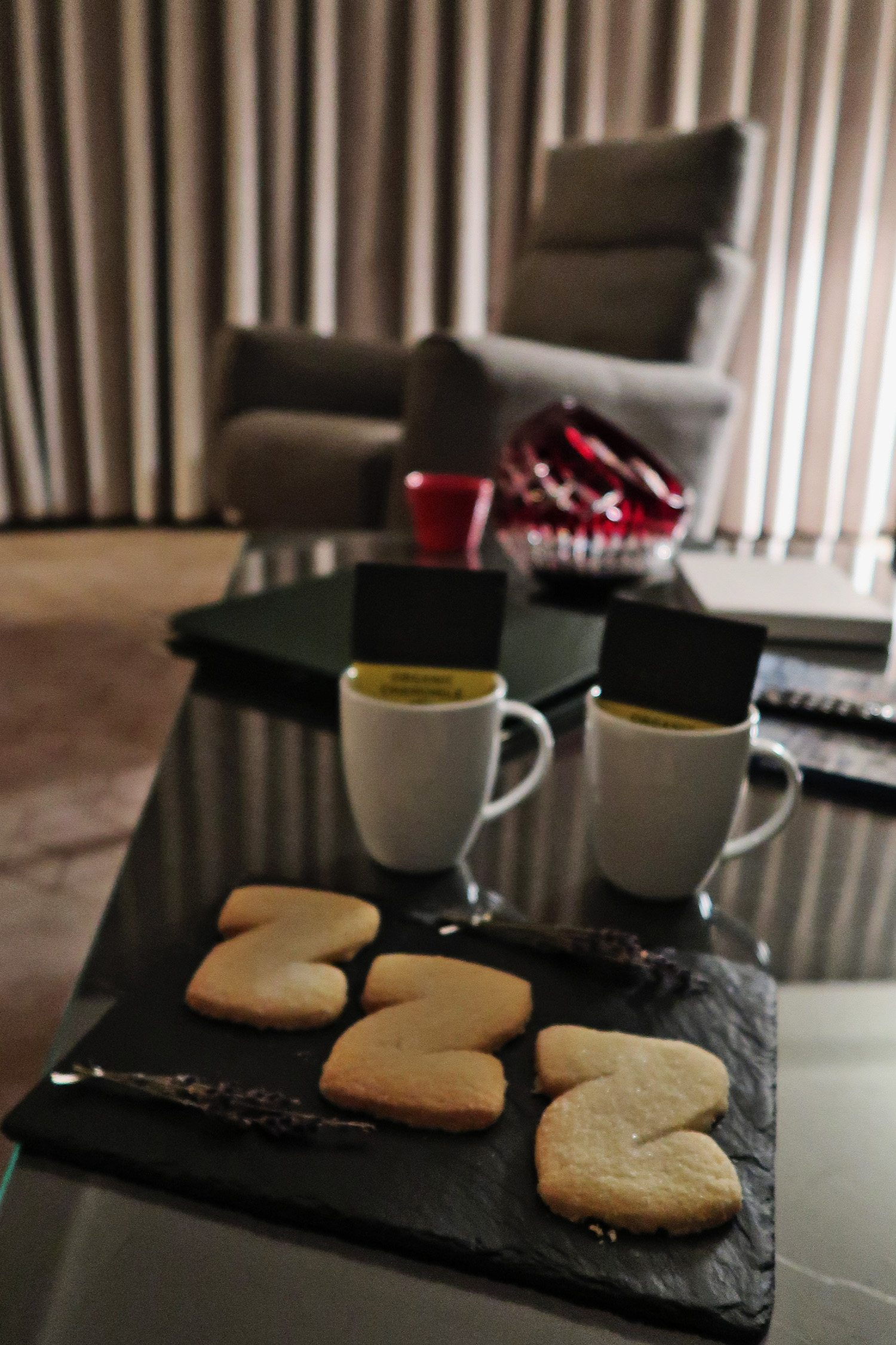 Plate of z-shaped biscuits and two mugs with tea bags in them placed on the coffee table in the suite