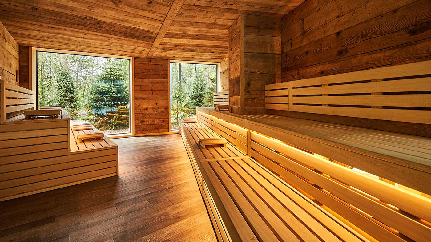 Interior of large wooden sauna with three layers of seating and windows looking out into forest