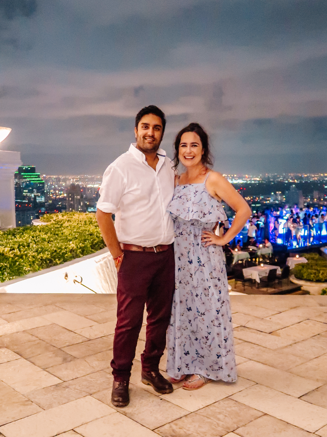 Inter-racial couple dressed smartly at a rooftop bar overlooking Bangkok skyline at night