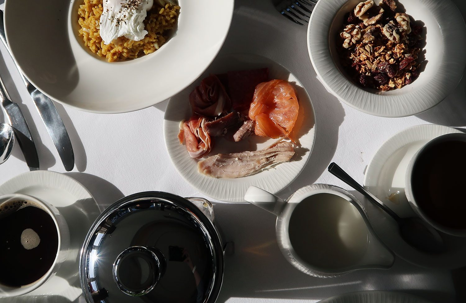 Top view of a table of breakfast dishes including kedgeree, poached egg, smoked salmon, meats, granola, coffee