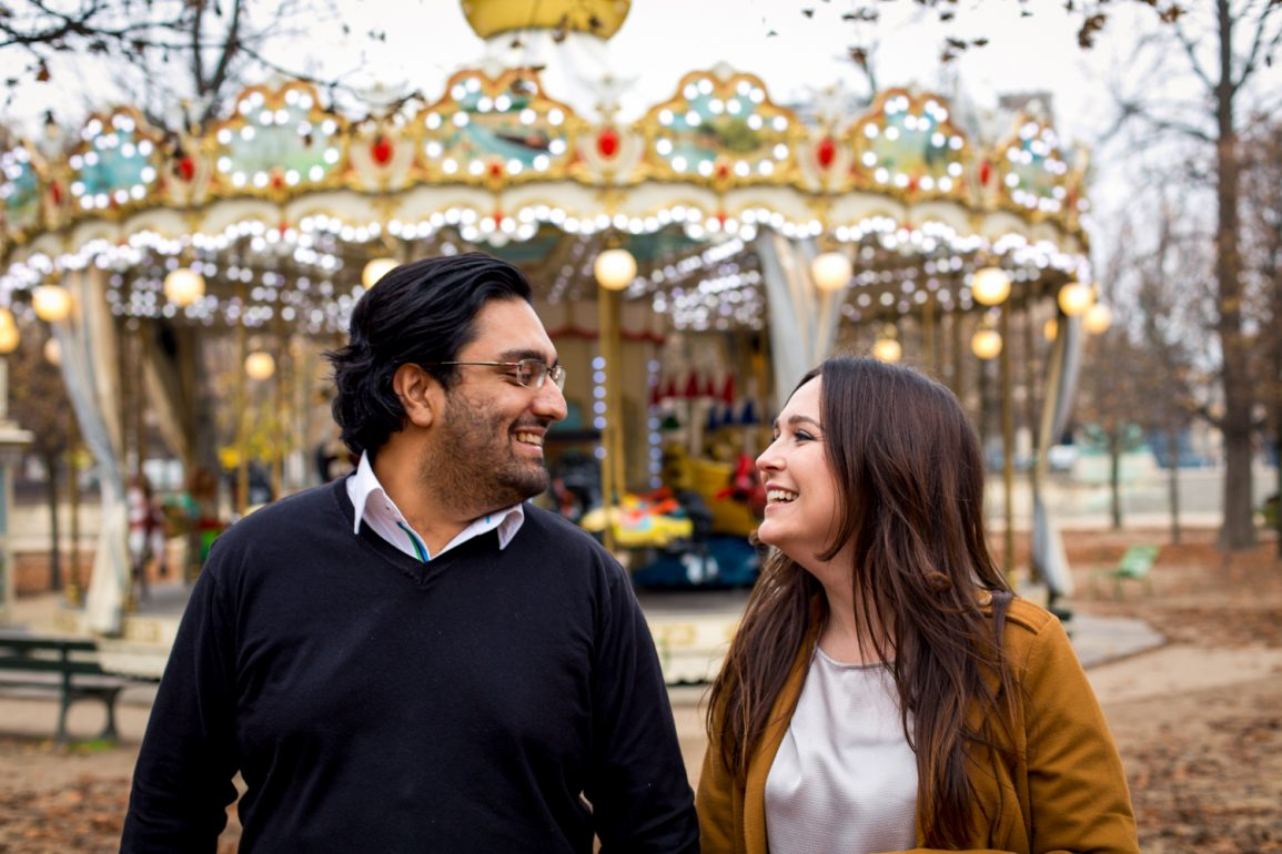 couple looking at each other smiling with traditional carousel in the background