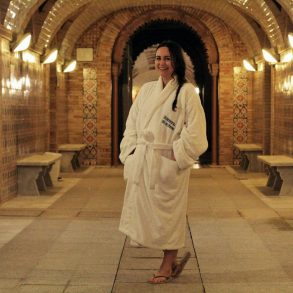 Woman wearing spa robe standing in tiled underground spa area