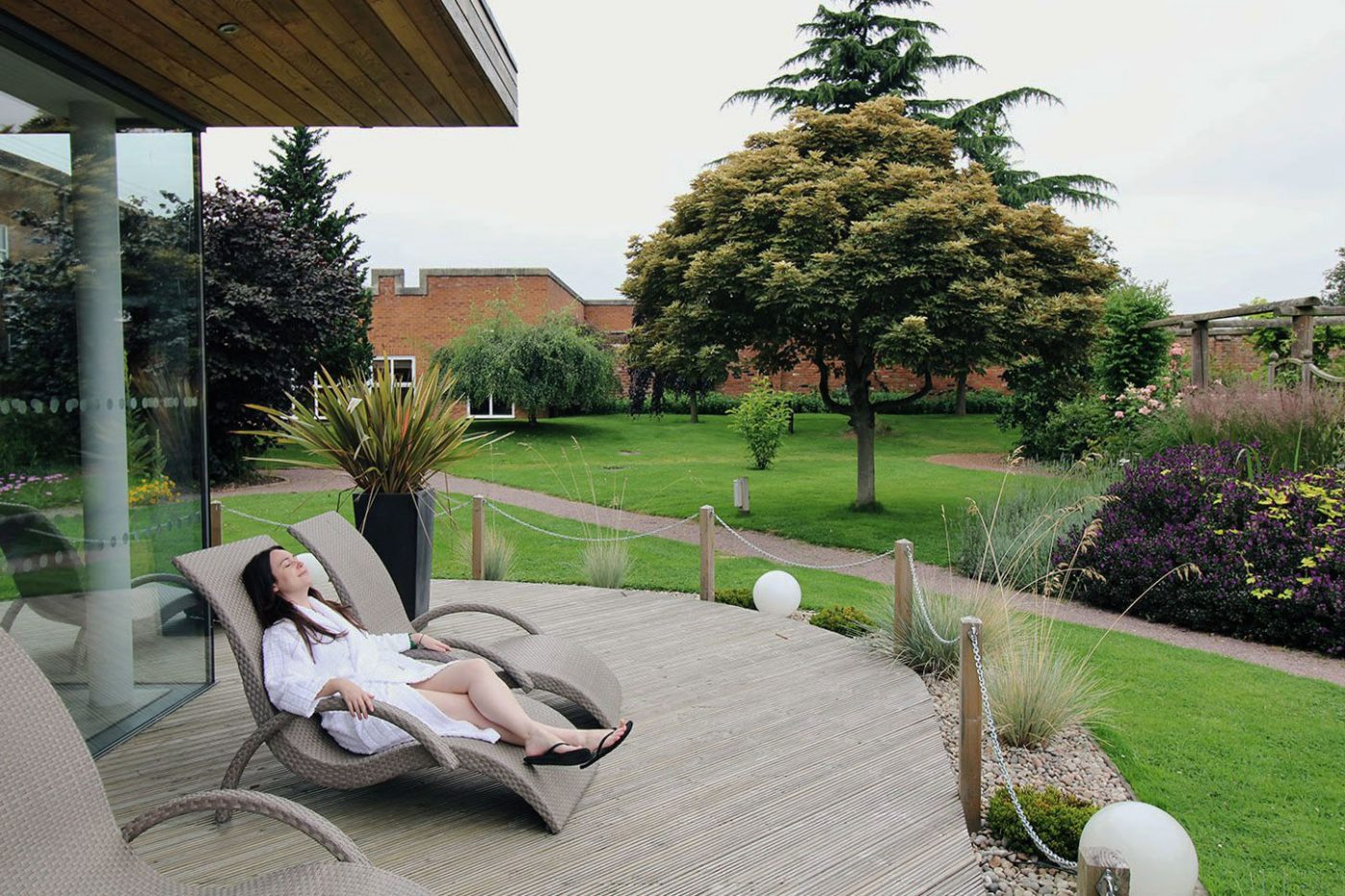 woman lying on sunbed in spa robe surrounded by gardens